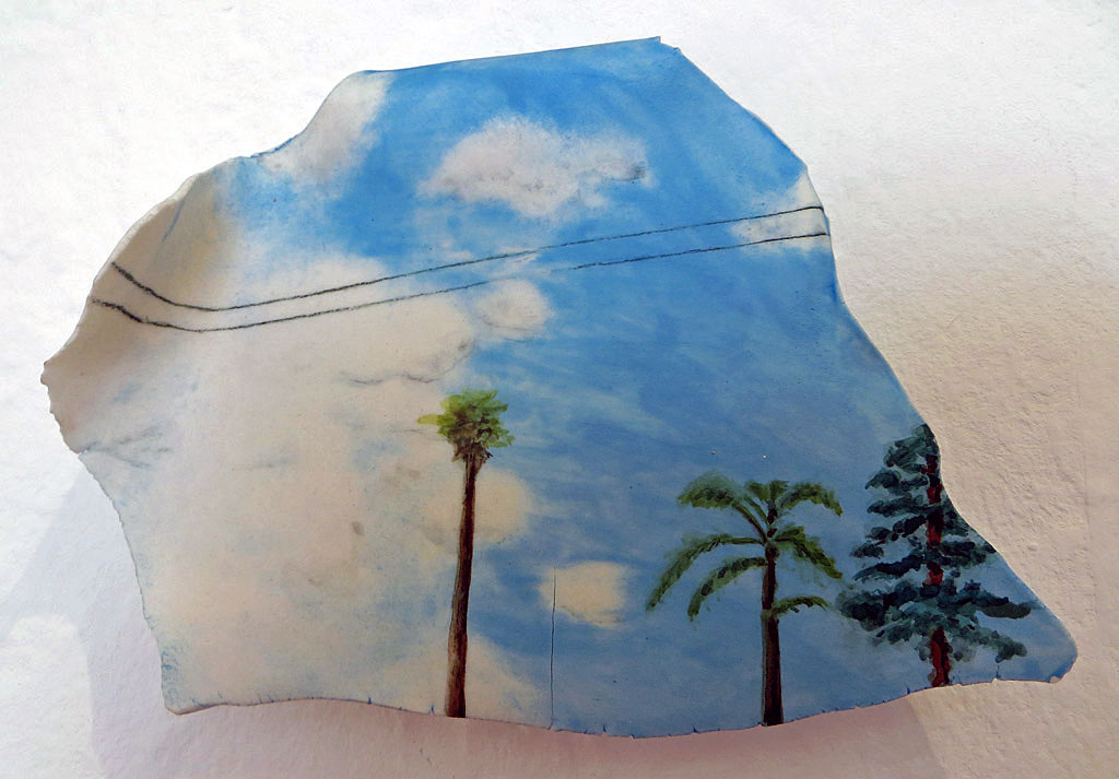 Small ceramic tile of sky, clouds, palm and pine trees