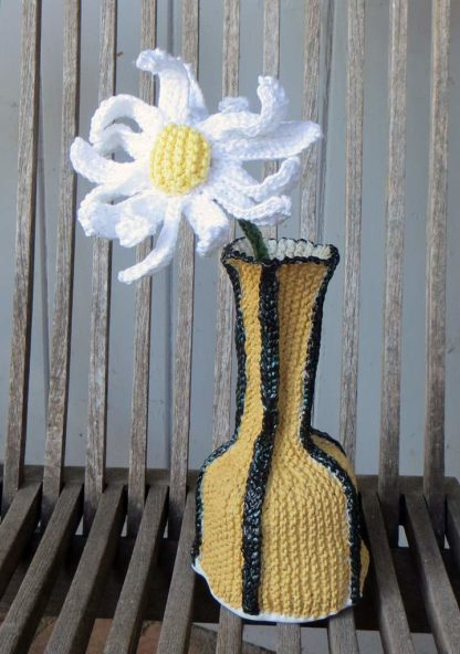 yellow black vase with knitted daisy